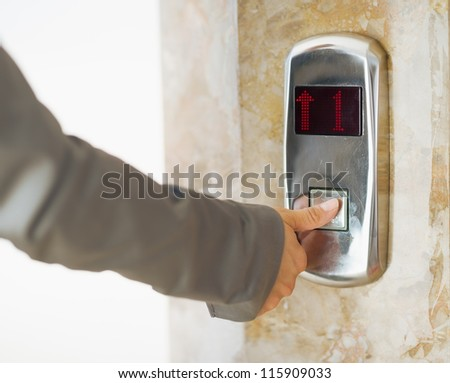 Closeup on business woman hand pushing elevator button