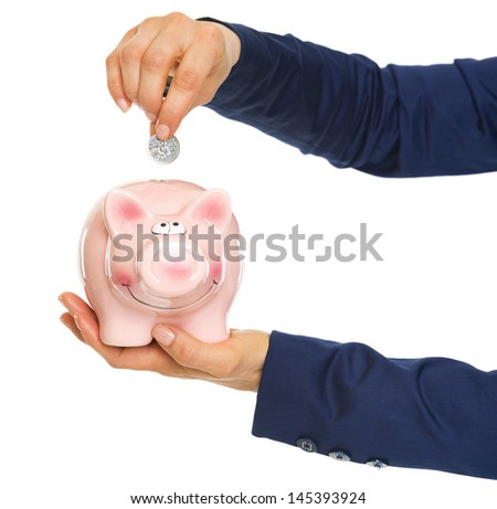 Closeup on business woman hands putting coin into piggy bank