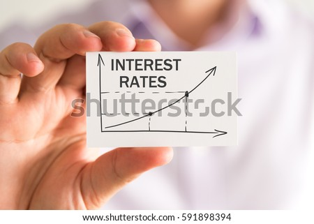 Closeup on businessman holding a card with INTEREST RATES rising arrow and chart, business concept image with soft focus background