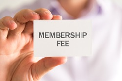 Closeup on businessman holding a card with MEMBERSHIP FEE message, business concept image with soft focus background
