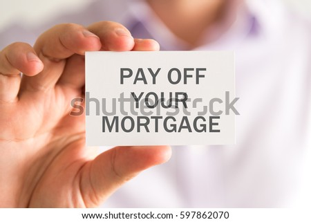 Closeup on businessman holding a card with PAY OFF YOUR MORTGAGE message, business concept image with soft focus background