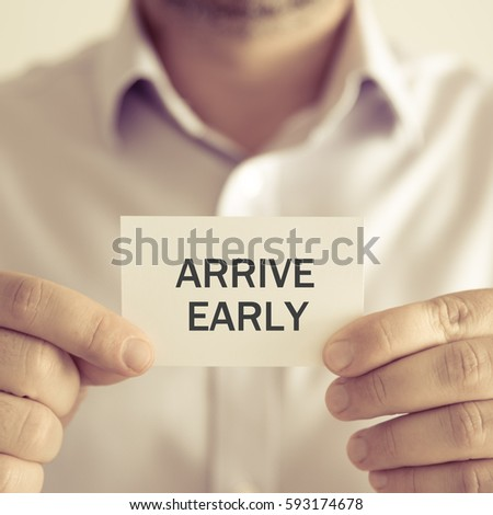 Closeup on businessman holding a card with text ARRIVE EARLY, business concept image with soft focus background and vintage tone