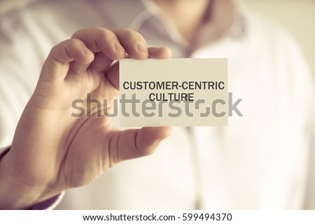Closeup on businessman holding a card with text CUSTOMER-CENTRIC CULTURE, business concept image with soft focus background and vintage tone