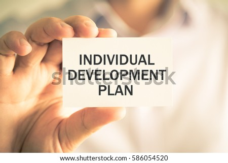 Closeup on businessman holding a card with text INDIVIDUAL DEVELOPMENT PLAN, business concept image with soft focus background and vintage tone Сток-фото ©