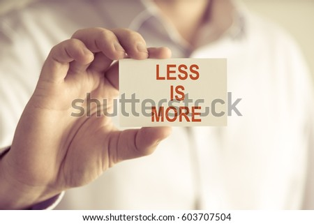Closeup on businessman holding a card with text LESS IS MORE, business concept image with soft focus background and vintage tone