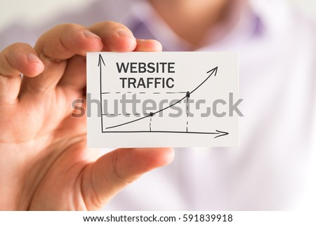 Closeup on businessman holding a card with WEBSITE TRAFFIC rising arrow and chart, business concept image with soft focus background #591839918