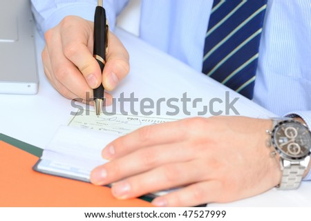 Closeup on businessman`s hands writing a check