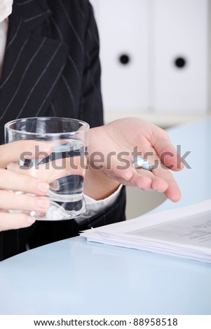 Closeup on caucasian hands holding pills and water in the office.