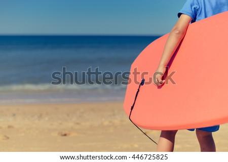 Closeup on child holding bodyboard, sunny beach outdoors background. #446725825
