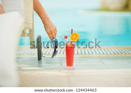 Closeup on cocktail near chaise-longue with relaxing woman