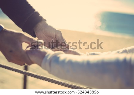 Closeup on couple in love Valentine day background. Happy lovers holding hands together with sunny outdoors.
