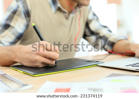 Closeup on designer using graphic tablet for photo editing