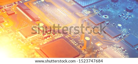 Closeup on electronic motherboard card in hardware repair shop. Blurred panoramic image with details of the circuitry and close-up on electronics. Filtered picture toned in orange and blue, copy-space #1523747684