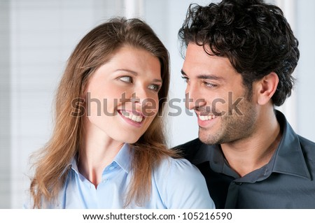 Closeup on faces of young couple smiling together with love