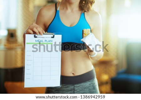 Closeup on fit sports woman in fitness clothes with fitness energy bar showing meal plan in the modern living room.