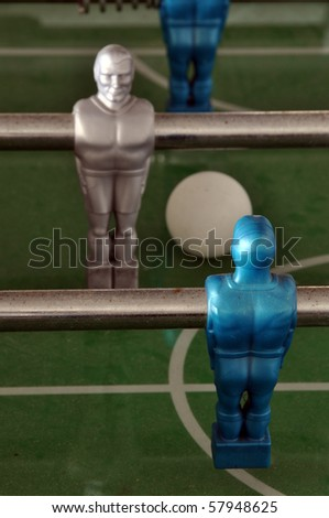 Closeup on foosball table with players, ball and central circle