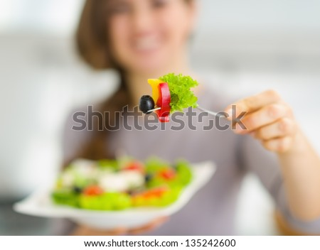 Closeup on fork with salad in hand of young woman