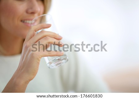 Closeup on glass of water held by woman\'s hand
