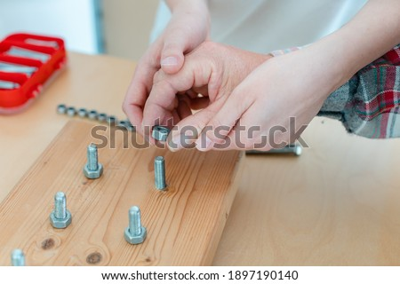 Closeup on hand of man in occupational therapy screwing nut on bolt Stock foto ©