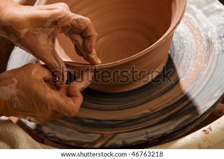 Closeup on hands of potter shaping clay on wheel