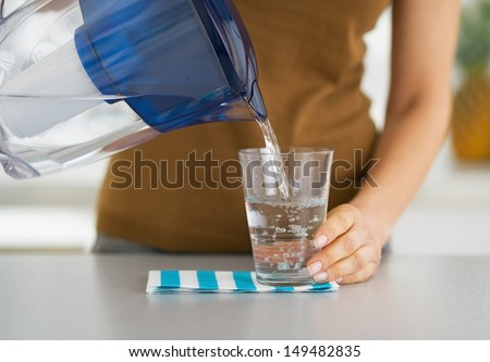 Closeup on housewife pouring water into glass from water filter pitcher
