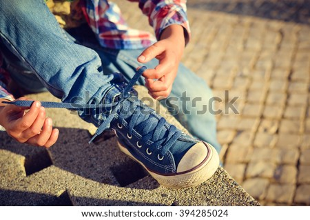 Closeup on kid hands tying laces ready for sport, school fun. Outside sunny background #394285024