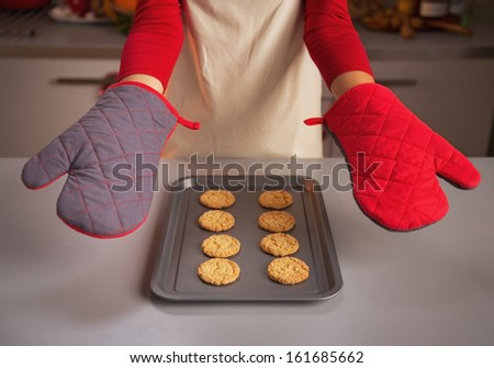 Closeup on kitchen gloves showing by young housewife and christmas cookies on pan