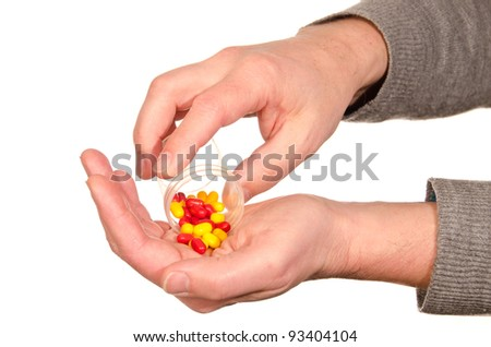 Closeup on man's hands with pills and pill container isolated on white background. - stock photo