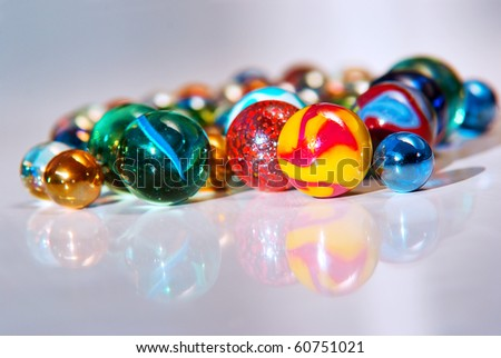 Closeup on many colorful glass marbles on a white surface