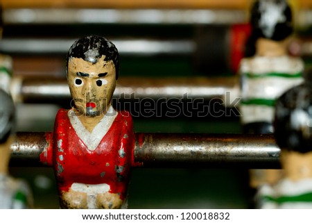 Closeup on miniature metallic ball players of a Foosball table soccer game