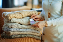 Closeup on modern female in white sweater and skirt sitting near couch with pile of sweaters and using cloth anti moth lavender wardrobe repellent in the modern house in sunny winter day.