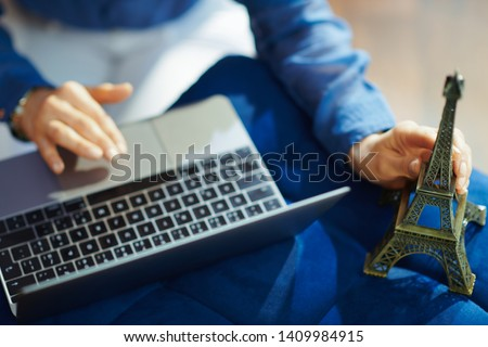 Closeup on modern woman holding a souvenir of the eiffel tower with laptop at modern home in sunny summer day. A fake website is made for illustrative purposes. #1409984915