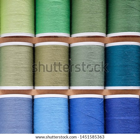 closeup on multi colored thread spools consist of green , gold , bronze and blue colors #1451585363