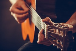Closeup on musical instrument. Young person holding guitar. Music sound hobby passion concept.