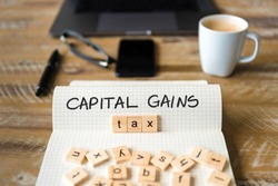 Closeup on notebook over vintage desk surface, front focus on wooden blocks with letters making Capital Gains Tax text. Business concept image with office tools and coffee cup in background