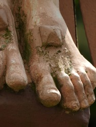 Closeup on one of the Five Holy Wounds (stigmata) of Jesus Christ as a large nail goes through foot covered with moss of an outdoor statue of the crucifixion in southwestern France, Occitanie