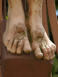 Closeup on one of the Five Holy Wounds (stigmata) of Jesus Christ as large nails go through feet covered with moss of an outdoor statue of the crucifixion in southwestern France, Occitanie