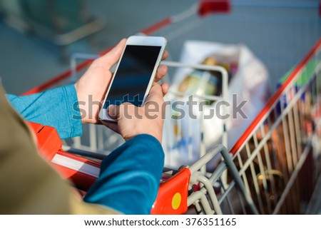 Closeup on person holding mobile phone in hand during shopping. Cart on store background