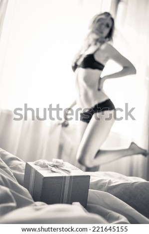 closeup on pink gift box present with one elegant blonde pinup pretty female in underwear having fun posing relaxing standing on light copy space background, black and white portrait