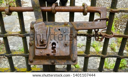 closeup on rusty vintage iron lock on outdoor fence of old house in Saint-Cirq Lapopie village, beautiful and historical medieval town in Occitan region, Lot Valley, southern France, Europe