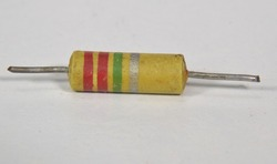 Closeup on single electronic resistor. Color bands tell us that the reistance of this component is 2.200.000 Ohms, or 2,2 MOhm with a tolerence of 10%