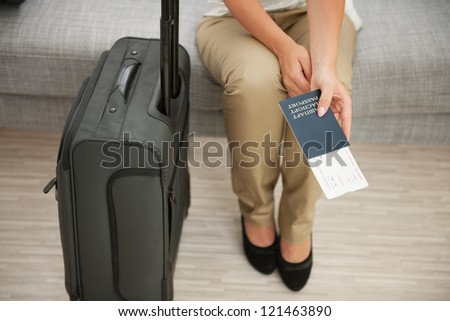 Closeup on suitcase and woman holding passport and air ticket