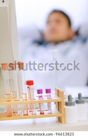 Closeup on table with test tubes and medical doctor in background