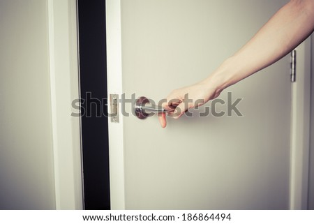 Closeup on the hand of a woman as she is opening a door at night