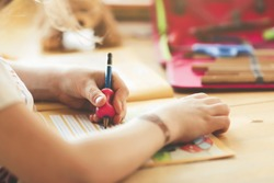 closeup on the hand of a young blonde left-handed girl training her handwriting at home in bright surrounding- homeschooling concept