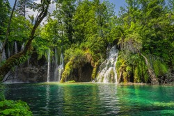 Closeup on waterfalls, covered in lichens illuminated by sunlight. Green lush forest in Plitvice Lakes National Park UNESCO World Heritage, Croatia