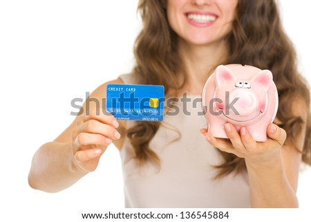 Closeup on woman holding credit card and piggy bank