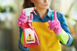 Closeup on woman in orange apron and pink rubber gloves with raised finger and spray bottle of cleaning toxic supplies in the living room in sunny day. toxic cleaning supplies concept