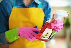 Closeup on woman in orange apron and pink rubber gloves with spray bottle of cleaning supplies reading instruction in the living room in sunny day. toxic cleaning supplies concept.