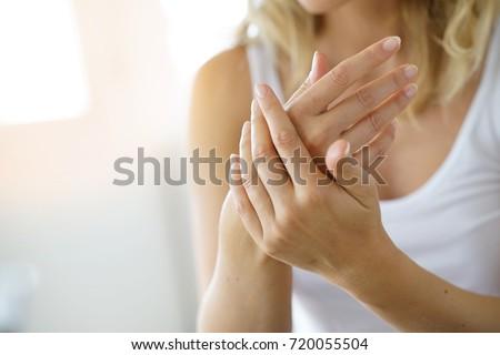 Closeup on woman's hands applying moisturizing hand-cream on
